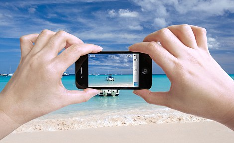 C1W97G Close up photo of a female tourist taking photos of a beautiful beach in The Bahamas with her iPhone 4 camera