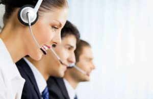 Three happy smiling young customer support phone operators at workplace